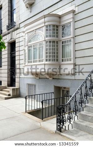 Wooden bay window and iron railing - stock photo
