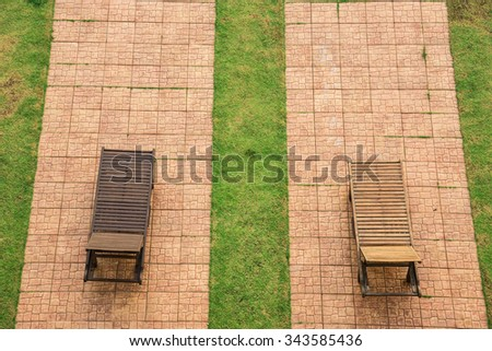 Wooden beach chairs at swimming pool - stock photo