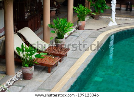 Wooden beach chairs beside indoor swimming pool. - stock photo