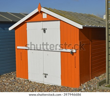 Wooden beach hut on shingle beach at Lancing, Near Brighton, West Sussex, England.