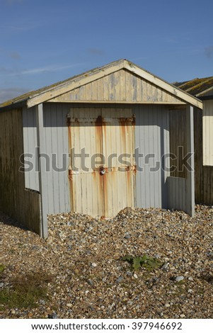 Wooden beach hut on shingle beach at Lancing, Near Brighton, West Sussex, England. With shingle piled up against door after storm