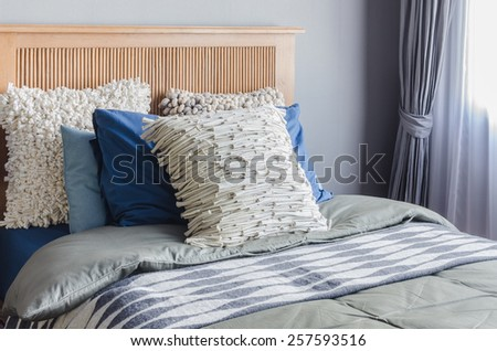 wooden bed with pillows in modern bedroom at home - stock photo