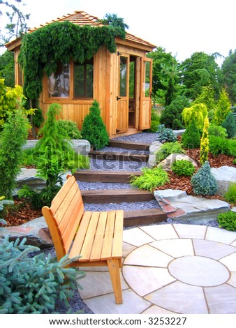Wooden bench and cabin in a garden - stock photo