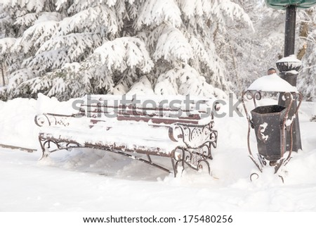 Wooden bench covered with snow in a winter park - stock photo