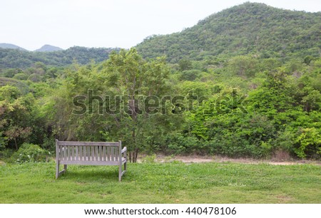 wooden bench in green garden lawn for resting and relax - stock photo
