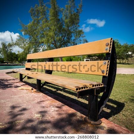 Wooden bench in park near caribbean lagoon - stock photo