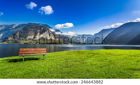 Wooden bench near the lake between by mountains - stock photo