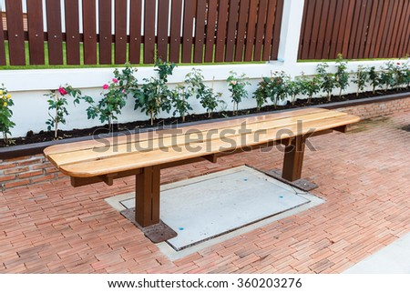 Wooden bench on footpath near wall