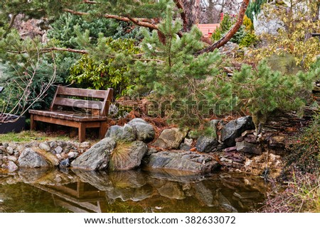Wooden bench on garden near pond - stock photo