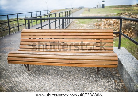 wooden bench on the coast on blue sky and cloud. sidewalk with handrails in perspective - stock photo