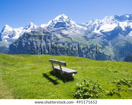 Wooden bench on the green field with the Eiger on the background, Jungfrau region, Switzerland