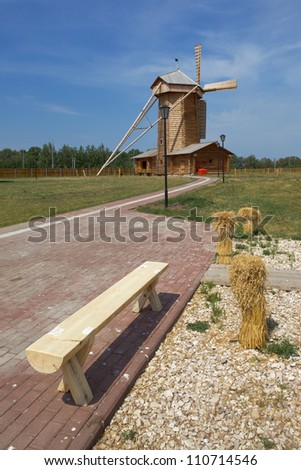 Wooden bench on the path leading to the windmills - stock photo