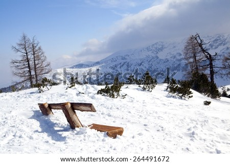 Wooden bench under snow in Austrian mountains - stock photo