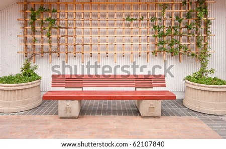 Wooden Bench with Plants and Wood Fence Background - stock photo