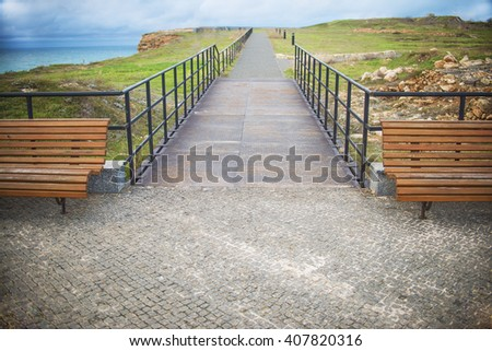 wooden benches on the coast on blue sky and cloud. sidewalk with handrails in perspective - stock photo