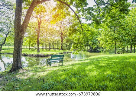 wooden benches overlook the tranquil canal, surrounded by lush greenery in the park in beautiful landscaped gardens.