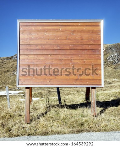wooden billboard in front of sky - nice background with space for text - stock photo