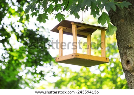 wooden bird feeder leaves trees - stock photo