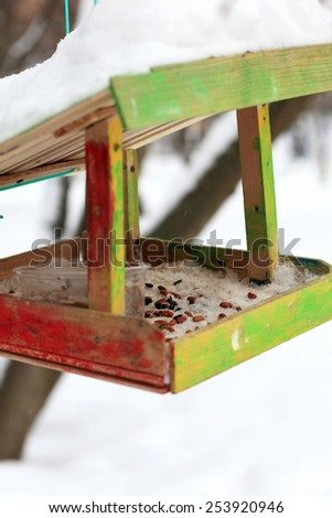 Wooden bird feeders in the winter park - stock photo