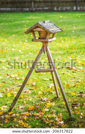 Wooden bird feeders in woods. - stock photo