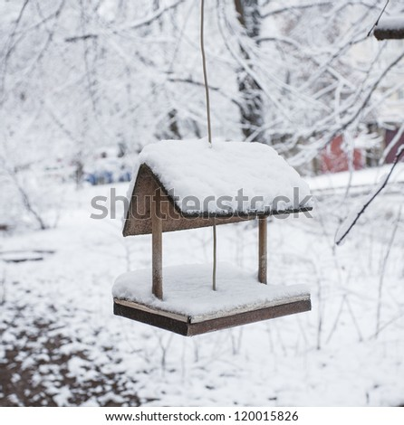 wooden bird table topped with fresh snow - stock photo
