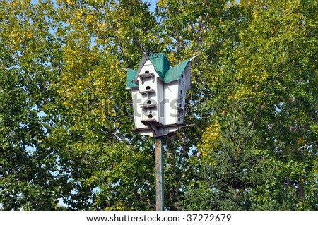 Wooden birdhouse high up among the trees - stock photo