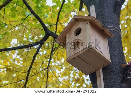Wooden birdhouse on the avenue autumn park - stock photo