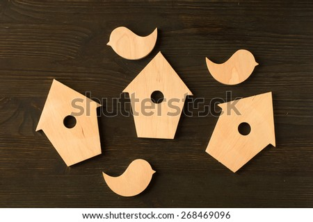 wooden birds and birdhouses on a black wooden background - stock photo