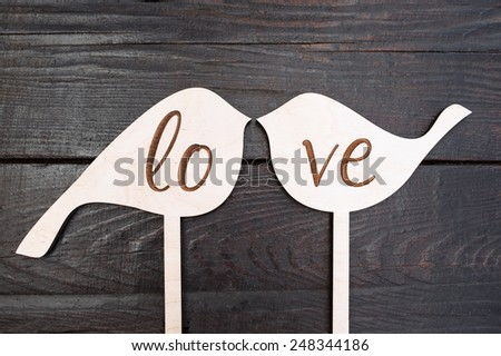 Wooden birds forming word LOVE - stock photo