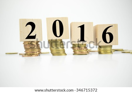 Wooden block with stacked coins with word 2016 written