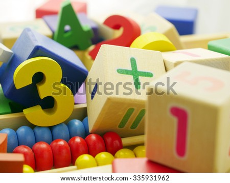 Wooden blocks and multicolor figures in a box.