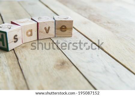 Wooden blocks are Save word on wooden floor - stock photo