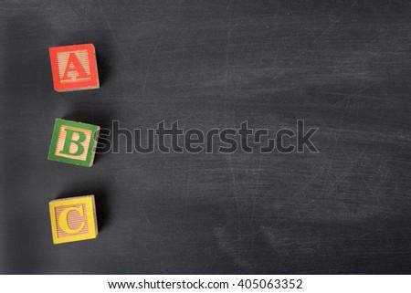 wooden blocks on blackboard letters ABC - stock photo