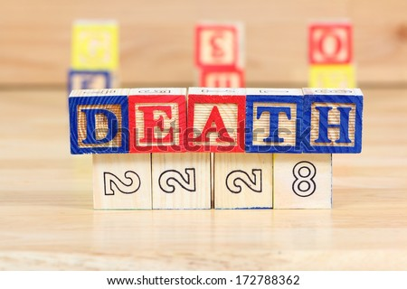 Wooden blocks with letters. Educational toy concept - children learning about death. - stock photo