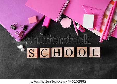 Wooden blocks with space for text and stationery on blackboard background