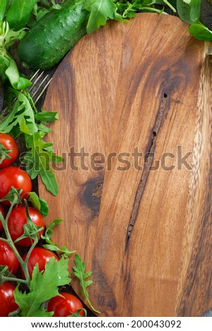 wooden board background, fresh lettuce and tomatoes, top view - stock photo