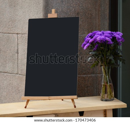 Wooden board for restaurant menu with empty space to add text standing at restaurant entrance with flower pot - stock photo