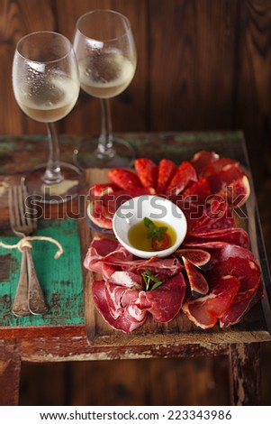 wooden board of Assorted Cured Meats, olive oil, fork and glasses of white wine on vintage stool - stock photo