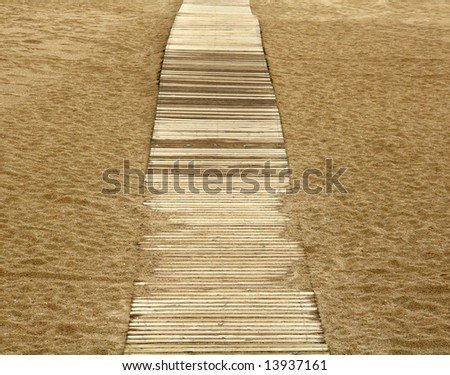 wooden boards path on the sand on a beach - stock photo