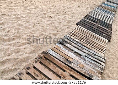 Wooden boards path on the sandy beach - stock photo