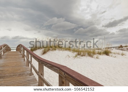 Wooden boardwalk footpath through the sand dunes to the ocean and beach at Gulf Islands National Seashore in Florida. - stock photo