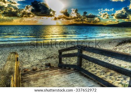 wooden boardwalk on the sand in Alghero, Sardinia - stock photo