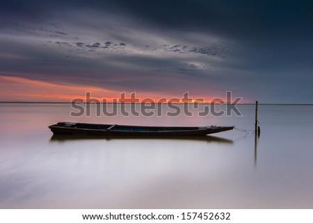 wooden boat bound at wooden pole at Jubakar Pantai, Tumpat, Kelantan East coast of Malaysia. - stock photo