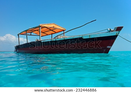 Wooden boat floating on the clear turquoise water of Zanzibar island - stock photo
