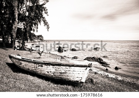 wooden boat on the beach in sepia - stock photo