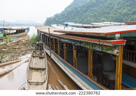 Wooden boat sailing over the Mekong river in Asia - stock photo