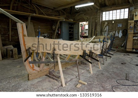 Wooden boat under construction. Small wooden boat under construction in traditional shipyard. Cantabric Sea,  Spain. - stock photo