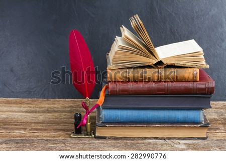 Wooden bookshelf  with pile of antique books and red feather pen - stock photo