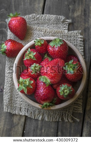 Wooden  bowl filled with fresh ripe red strawberries, from above - stock photo