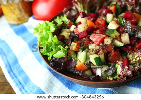 Wooden bowl of fresh vegetable salad on table, closeup - stock photo